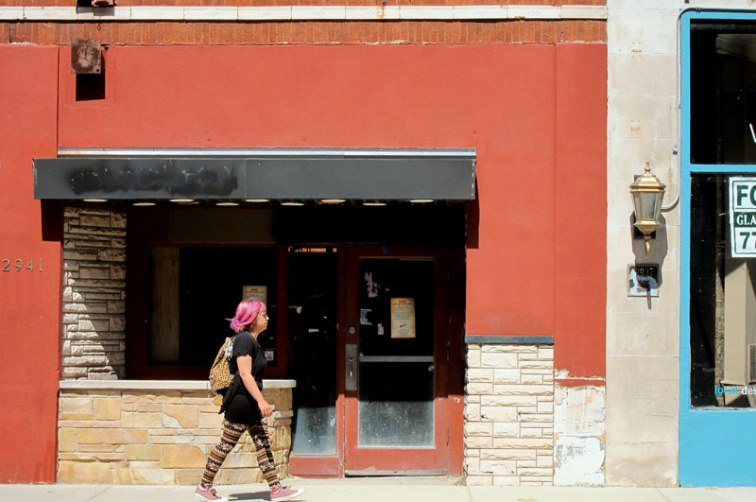 Pink haired woman with argyle leggings and pink sneakers walking past a long neglected storefront on a North Clark Street, Chicago